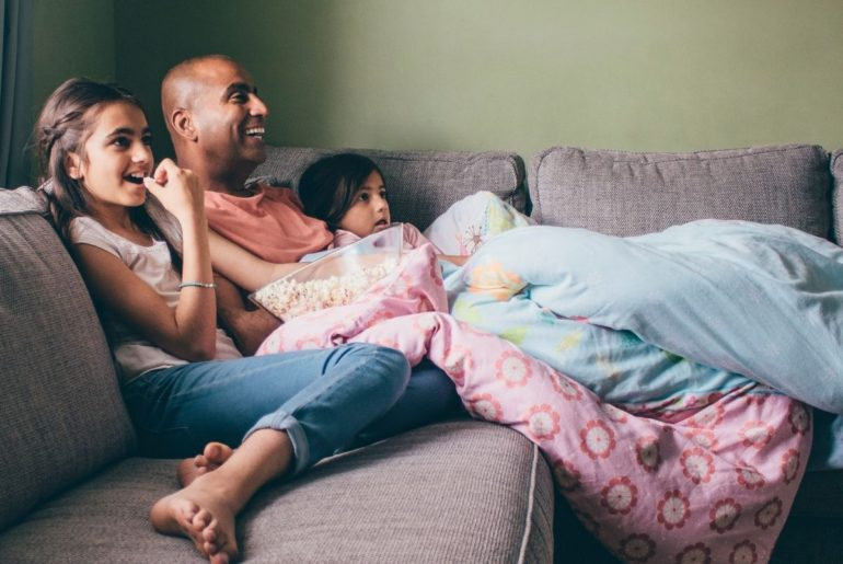 Father and kids enjoying family movie night.