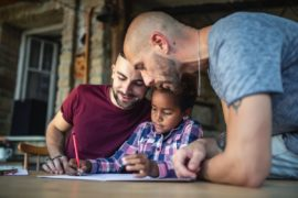Same sex couple helping adopted daughter with homework.