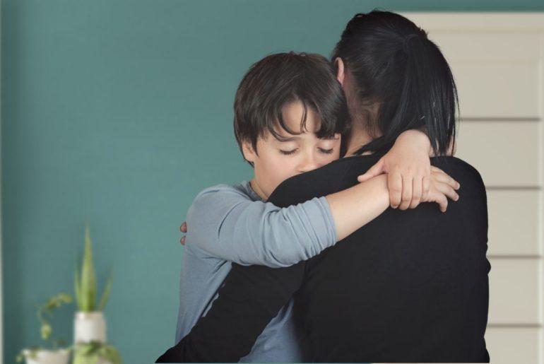 Mother hugging sad child.