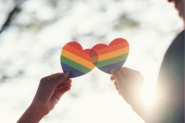 Two people holding Pride hearts with sun in background.