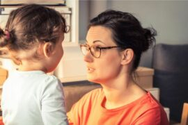 Mom crouched down to talk seriously with young child.