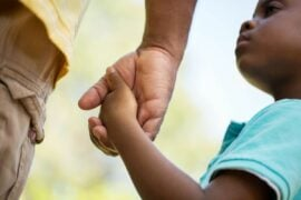 Boy holding dad's hand.