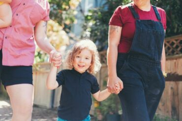 Parents with young child walking outdoors.