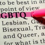 Close up of pink highlighter marking the word LGBTQ in dictionary.