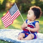 Baby looking at American flag.