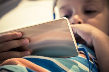 Child staring at smartphone screen.