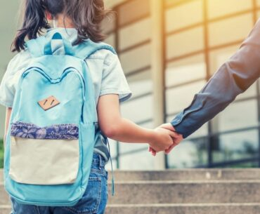 Girl wearing backpack on school steps holding parent's hand.