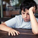 Discouraged boy sitting alone.