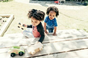 Two young kids playing with toy cars outside.