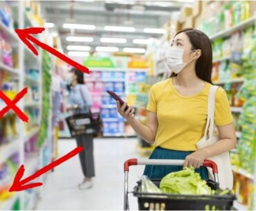 Masked woman looking at products in a grocery store aisle.