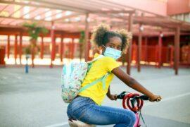 Girl wearing mask riding her bike to school.