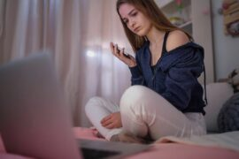 Worried teen girl sitting on bed looking at laptop.