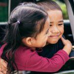 Siblings hugging and smiling in car window.