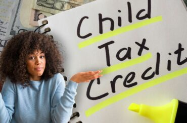 Woman shrugging over Child Tax Credit writing on notebook in background.