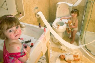 Twin toddlers making a huge mess in the bathroom.