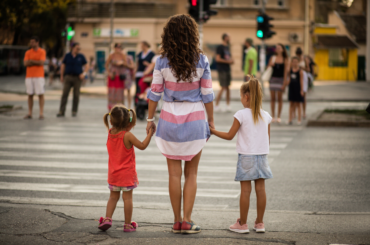 Mother and two children waiting at a crosswalk.