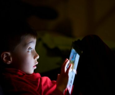 Boy looks scared using tablet in the dark.