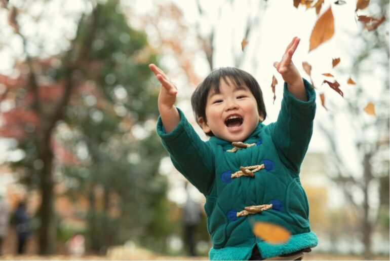 Young boy playing in autumn leaves.