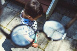Perspective of adult putting on glasses to see young child.