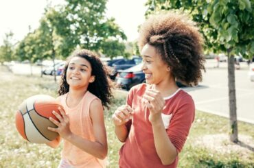 Teen girls playing basketball outdoors.